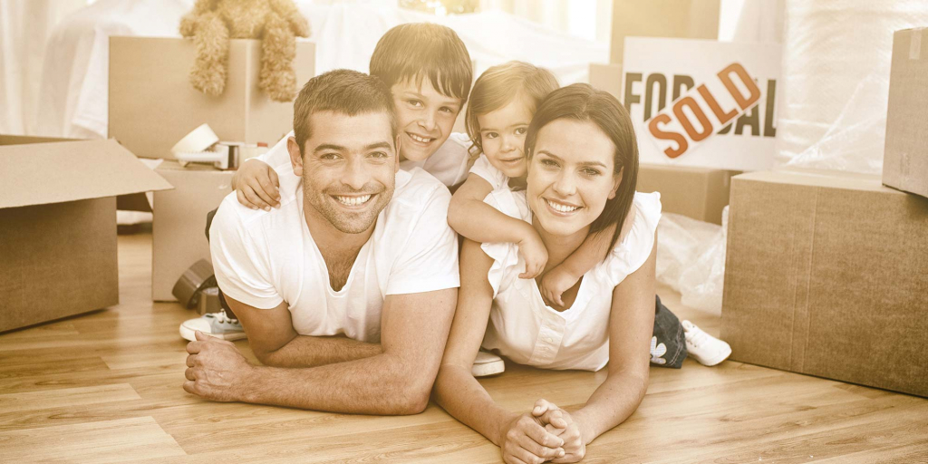 A family of four lays on the floor with a sold sign behind them
