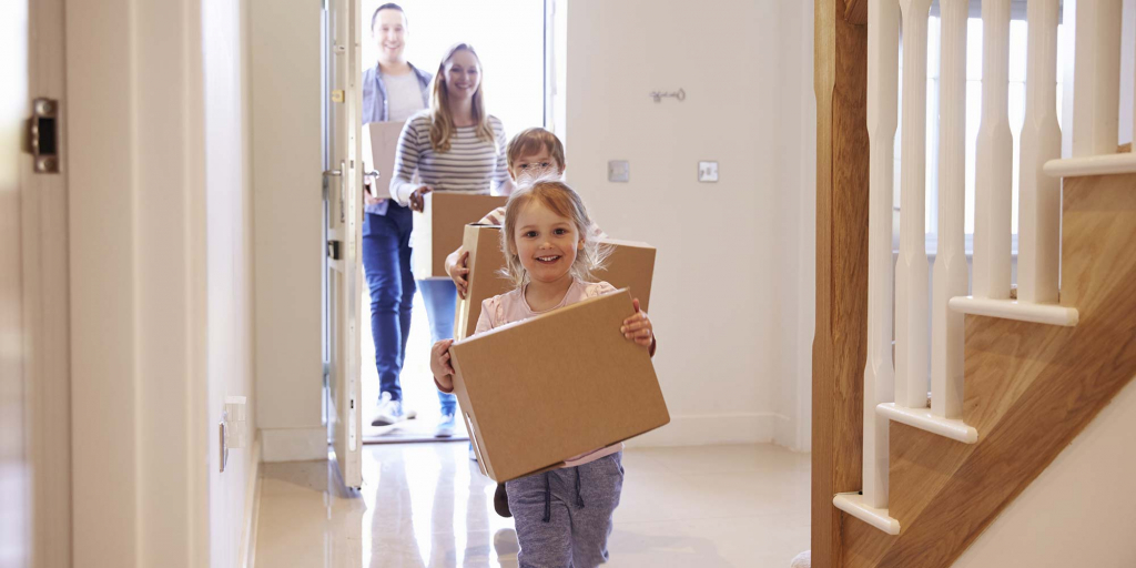 A family of four enter a foyer with boxes