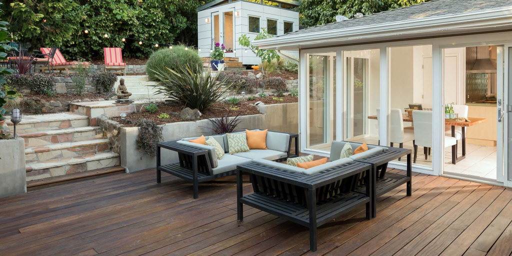 A well furnished back porch leads to a sunroom