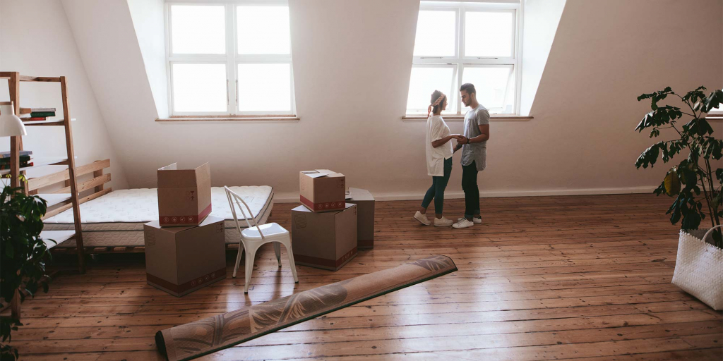 A young couple in a large loft unpacking their home