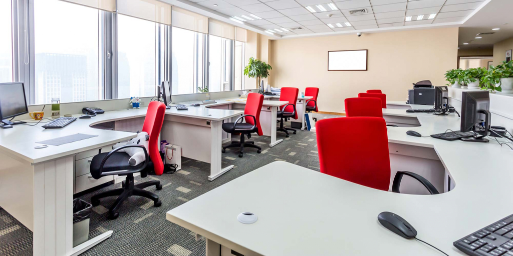 A bright vibrant office with conjoined desks and red chairs