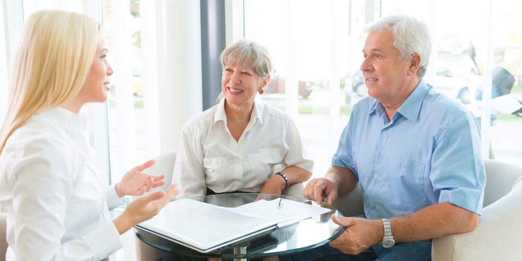 A realtor sits with an older couple to discuss paperwork