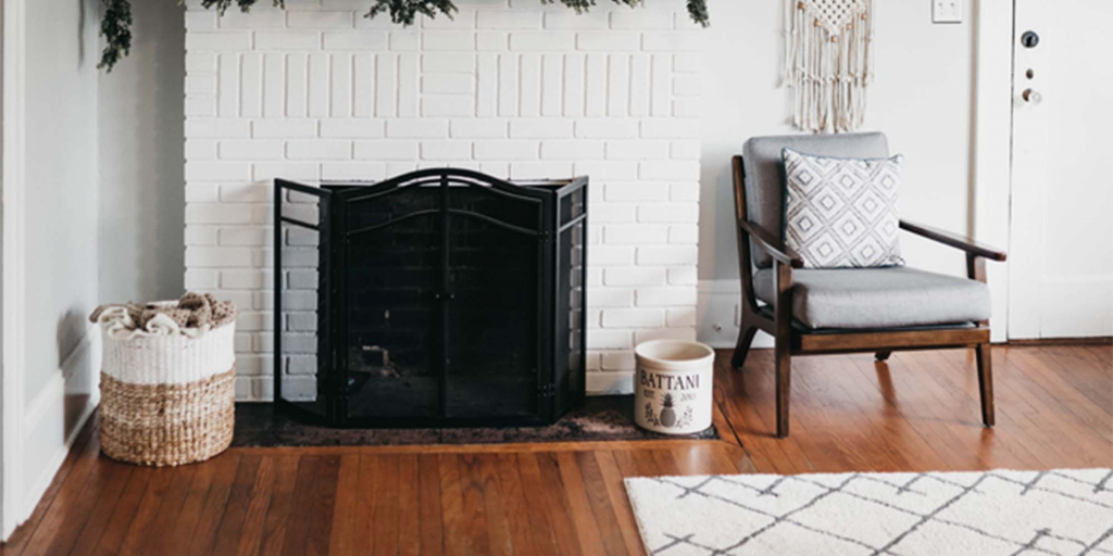 A black grate covers a white brick fireplace near the front door of the home.