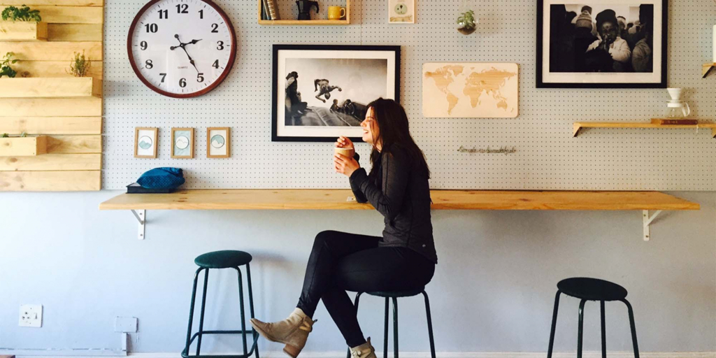 A woman enjoys coffee at a rustic counter